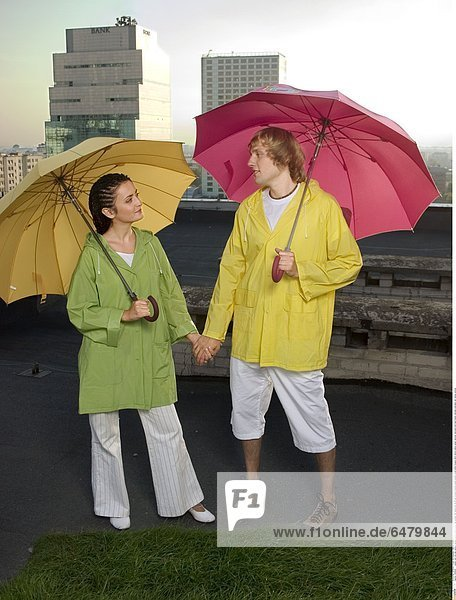1229545 outdor roof city day summer spring people couple young man woman fair haired boy 20-25 girl woman brunette pigtail pigtails stand white trousers short shorts yellow green raincoat raincoats hold hand hands umbrella umbrellas rain raining vertical