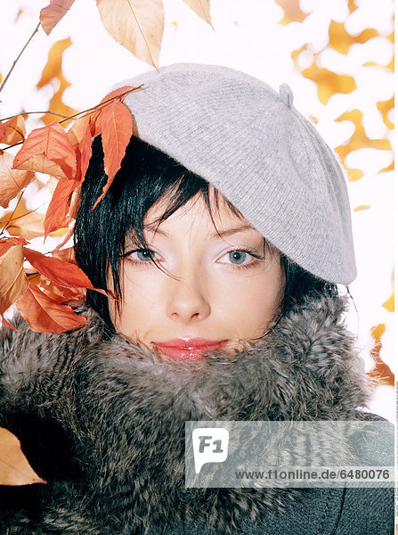 1228812 indoor studio people woman young 25-30 brunette fringe portrait close up fashion autumn coat grey make up lip lips vertical leaf leaves orange cap fur collar smile smiling