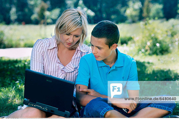 1228640 outdoor day summer people woman 35-40 mature blonde blouse white stripe stripes striped lie laptop internet personal computer notebook communication rest relax field sit smile smiling horizontal write show vacation boy son 10-15 dark haired hair blouse blue trousers jean jeans