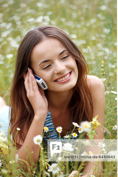 1228742 outdoor day summer people woman girl young 20-25 brunette long haired hair meadow field rest relax vacation smile smiling lie talk conversation mobile phone cell cellular cellphone telephone communication telecommunication vertical close up
