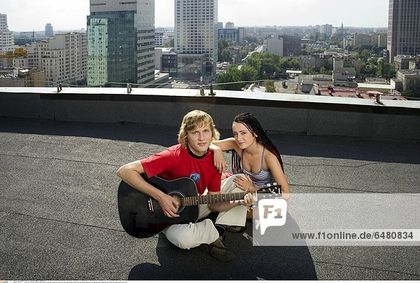 1229492 outdor roof city day summer people couple young man woman fair haired boy 20-25 girl woman brunette long hair pigtail pigtails sit cross leg legs smile smiling hold play guitar instrument musical horizontal
