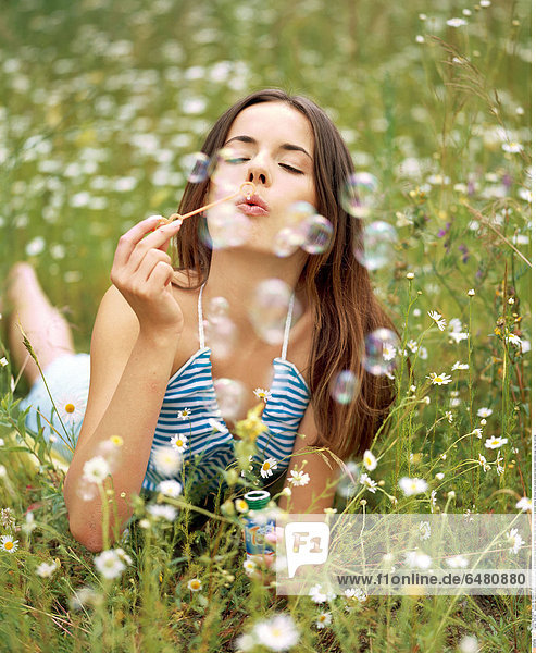 1228740 outdoor day summer people woman girl young 20-25 brunette long haired hair meadow field rest relax vacation smile smiling lie blouse stripe stripes striped blue bubble bubbles soap play fun vertical