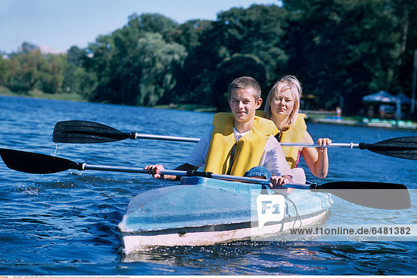1228649 outdoor day summer people woman mother boy child 35-40 blonde dark haired hair 10-15 water lake river tree trees vacation recreation rest relax canoe oar oars life jacket horizontal smile smiling life jackets son