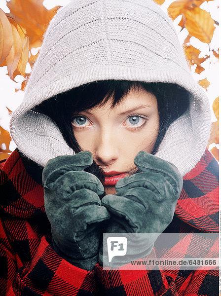 1228846 indoor studio people woman young 25-30 fringe brunette portrait close up fashion autumn hood glove gloves grey jacket pane paned red black make up lip lips vertical