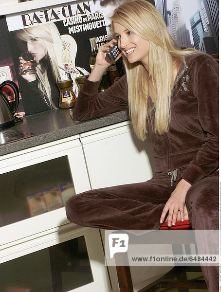 1221003 indoor flat kitchen young woman 25-30 blonde long hair sit chair brown trousers blouse track suit smile smiling hold receiver stationary telephone phone call speak talk cordless communication telecommunication close up vertical