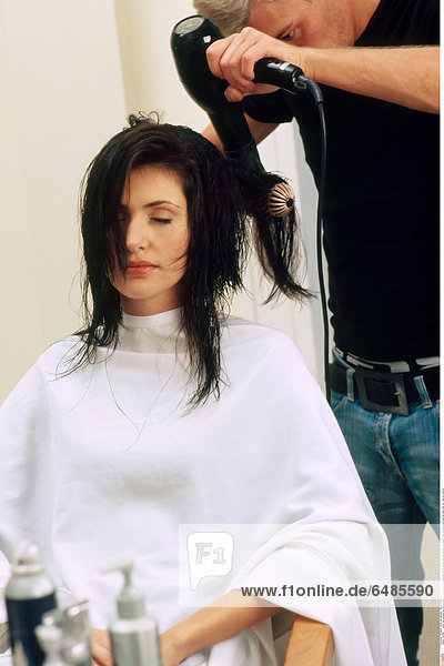 1221980 indoor hair-dressing hair dressing salon couple young man hairdresser 25-30 woman long hair brunette wet beauty care sit stand hold brush hair-drier drier dry close up vertical