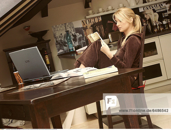 1221067 indoor flat room young woman blonde long hair ponytail 25-30 sit chair table brown blouse laptop notebook personal computer work internet communication book books hold read profile horizontal
