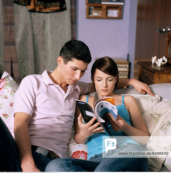 1222806 indoor flat room people woman man young girl boy 20-25 couple brunette fringe dark haired blouse pink blue rest relax vertical horizontal hold newspaper read hobby close up trousers jean jeans sit sofa couch