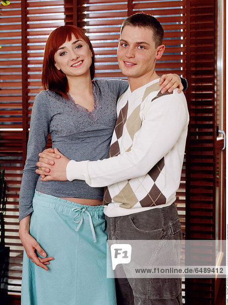 1235867 indoor flat room people young woman 25-30 red fringe dark haired stand couple smile smiling dress blue sweater grey pattern patterns embrace vertical man