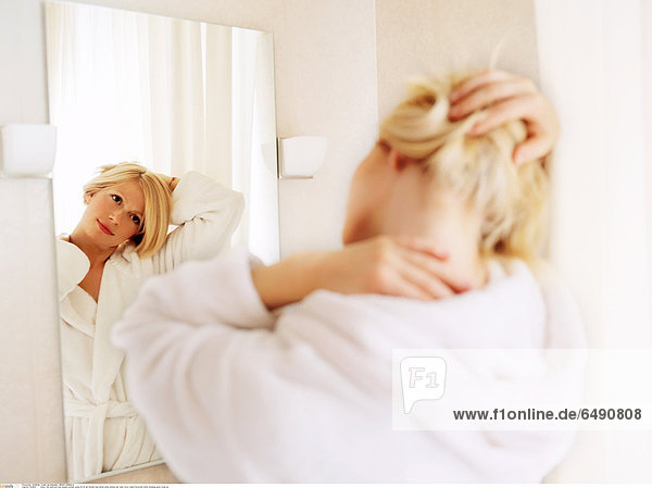 1234814 indoor flat bathroom bed people woman young 20-25 girl blonde long haired smile smiling rest relax mirror stand horizontal white dressing gown close up