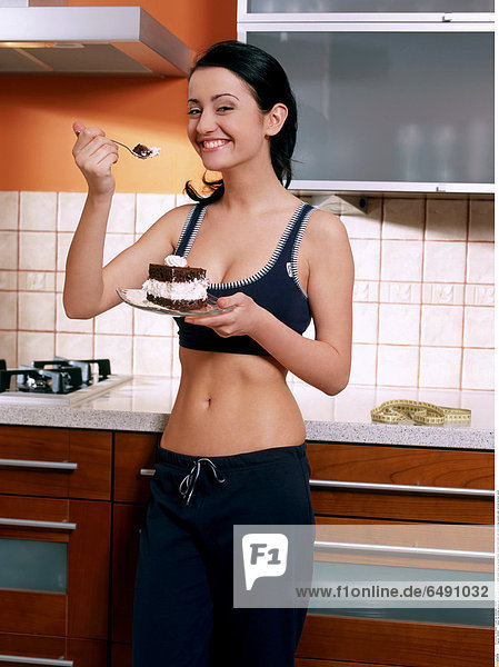 1235907 indoor flat kitchen people woman young 25-30 brunette stand close up blouse black trousers hold plate eat smile smiling sweets cake vertical stomach navel