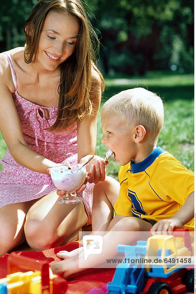 1236502 outdoor summer spring day people son child boy 0-5 fair rest relax blouse yellow dress pink play fun mother woman brunette long haired smile smiling toy toys eat ice cream vertical