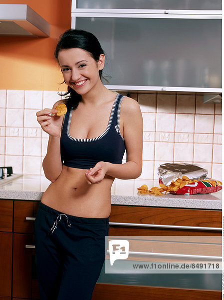 1235910 indoor flat kitchen people woman young 25-30 brunette stand close up blouse black trousers hold plate eat smile smiling sweets cake vertical crisps crisp stomach navel