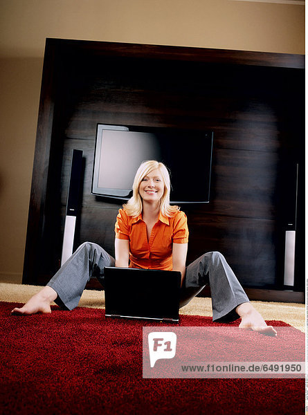 1234765 indoor flat room people woman young 20-25 girl blonde long haired foot feet barefoot vertical trousers jean jeans blouse orange laptop internet communication personal computer smile smiling
