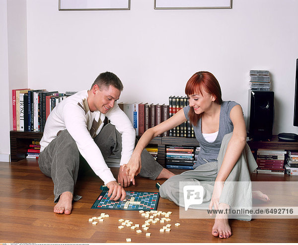 1235879 indoor flat room people young woman 25-30 red fringe dark haired couple sit foot feet barefoot play rest relax smile smiling blouse white trousers green scrabble horizontal