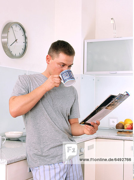 1235874 indoor flat kitchen people young 25-30 man dark haired stand pyjamas blouse grey tshirt t-shirt drink mug coffee tea read rest relax newspaper vertical