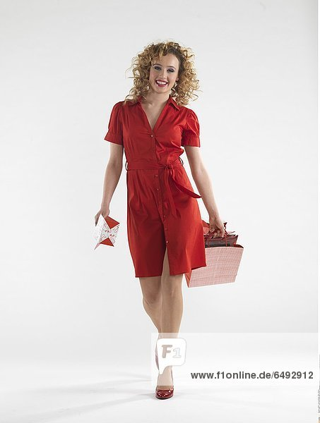 1236081 indoor studio woman people 20-25 girl young blonde long haired smile smiling hold show present presents gift gifts dress red vertical