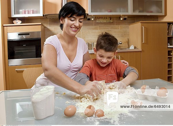 1235617 indoor flat kitchen people child boy 5-10 fair haired blouse orange table egg eggs glass water make cake flour break close up smile smiling mother woman mature 30-35 brunette blouses pink horizontal