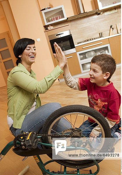 1235594 indoor flat room floor people child boy 5-10 fair haired sit bike fragment blouse red trousers jean jeans blue repair play fun mother woman 30-35 mature brunette blouses green vertical smile smiling hand hands touch