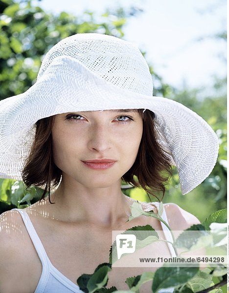 1236867 outdoor summer day people woman young 20-25 girl brunette fringe blouse white portrait close up vertical smile smiling hat