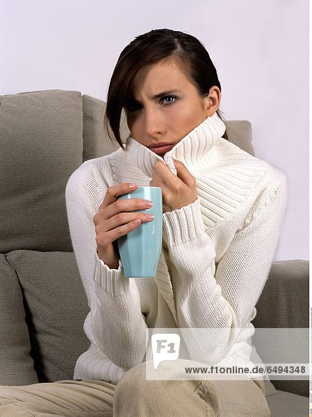1239362 indoor flat room sit sofa people woman brunette young 20-25 girl sweater white close up sad sadness think hold mug drink tea coffee cold illness vertical