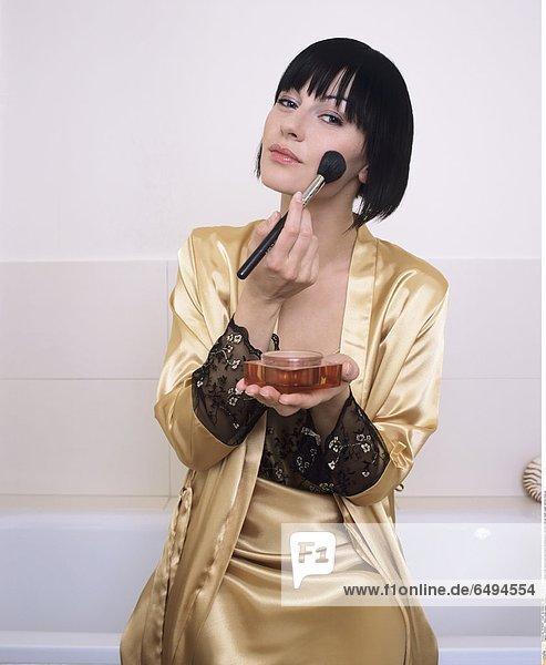 1239133 indoor studio people woman young girl 20-25 brunette fringe blouse satin gold black dressing gown vertical make up cheek rouge vertical close up