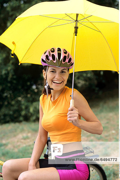 1239299 outdoor day summer vacation people woman young 20-25 girl smile smiling close up blouse orange sit park relax rest bike ride sport helmet hold umbrella yellow vertical trousers pink shorts