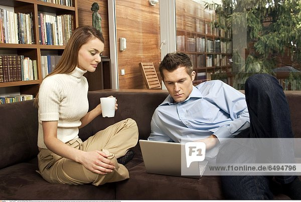 1237082 indoor flat room people couple young woman girl 20-25 brunette long hair sit couch sofa man dark haired 25-30 jean jeans trousers shirt blue jersey white beige cross leg legs hold mug drink laptop notebook personal computer work internet communication smile smiling close up horizontal