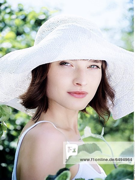 1236881 outdoor summer day people woman young 20-25 girl brunette fringe blouse white portrait close up vertical smile smiling hat