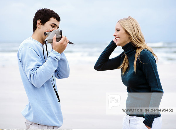 1240974 outdoor summer day people beach sand vacation rest relax woman 20-25 girl blonde long haired sweater turtleneck blue close up couple man 25-30 dark haired sweaters profile profiles hand pocket smile smiling hold hand hands camera take photo photos picture pictures