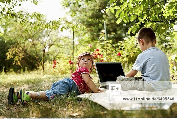1243628 outdoor day summer people child boy 5-10 fair haired blouse white trousers grey personal computer laptop internet communication sit blanket rest relax read write girl 0-5 blonde cap pink blouse pattern patterns trousers jean jeans sandal sandals sister brother siblings horizontal lie