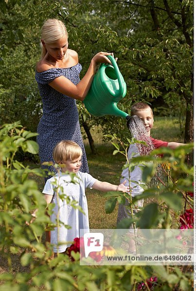 1243662 outdoor day summer garden people child boy 5-10 fair haired tree trees rest relax smile smiling blouse red white woman young 25-30 blonde long haired dress blue watering can cans water stand vertical flower flowers children girl 0-5 blondes