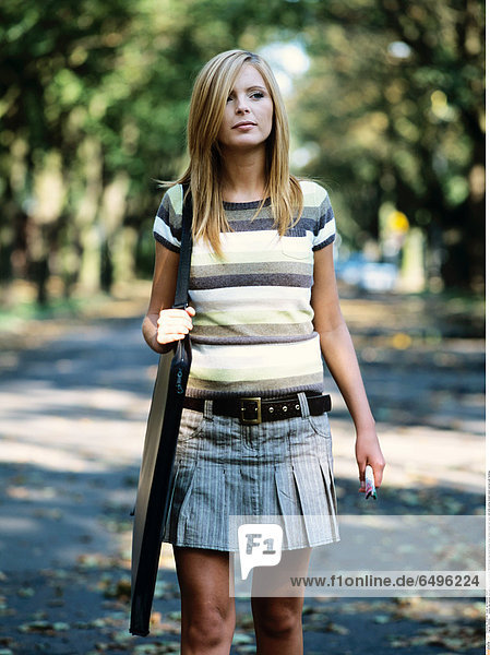 1243430 outdoor day summer park people woman young girl 20-25 blonde long haired blouse stripe stripes striped skirt grey hold smile smiling student stand vertical walk handbag