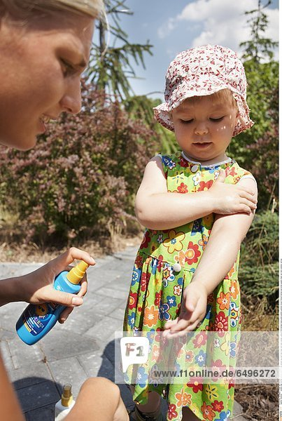 1243638 outdoor day summer people child 0-5 girl blonde cap pink tree trees rest relax woman young 25-30 blondes dress green pattern patterns flower flowers blonde hold bottle splash cream sun care cosmetic vertical