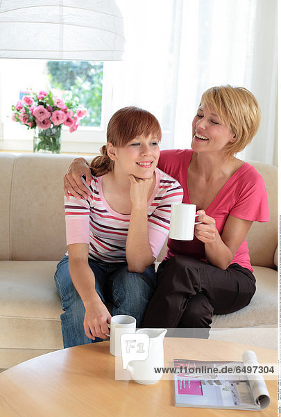 1244742 indoor flat room people woman women girl young 20-25 blonde long haired fringe mature 40-45 mother daughter blouse pink stripe stripes striped rest relax hold mug mugs drink coffee tea newspaper table talk conversation embrace smile smiling vertical close up