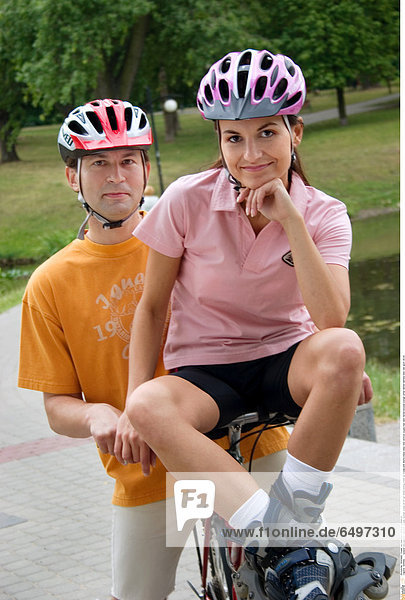 1245082 outdoor day summer vacation people woman young 20-25 girl smile smiling close up blouse pink shorts black relax rest vertical couple man dark haired blouses orange white helmet helmets bike ride sport 25-30