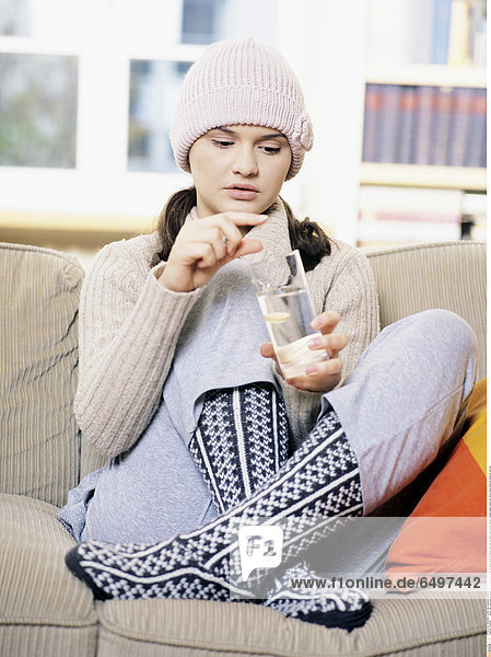 1245208 indoor flat room people young woman brunette 25-30 sit sofa couch ill illness cold cap sweater sock socks design designs glass water put throw drug medicine dissolve vertical