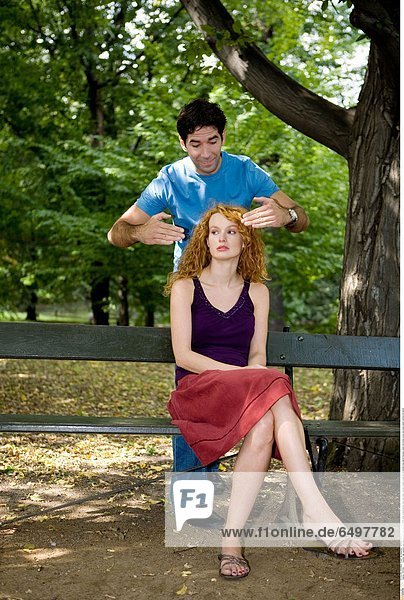 1247292 outdoor day summer park people man dark haired 25-30 smile smiling blouse blue rest relax woman couple young 20-25 blonde long haired blouses violet red dress cover eye eyes stand vertical sit bench