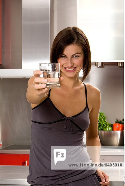 1247197 indoor flat kitchen people woman young 25-30 brunette close up blouse grey hand hold glass water drink diet smile smiling vertical