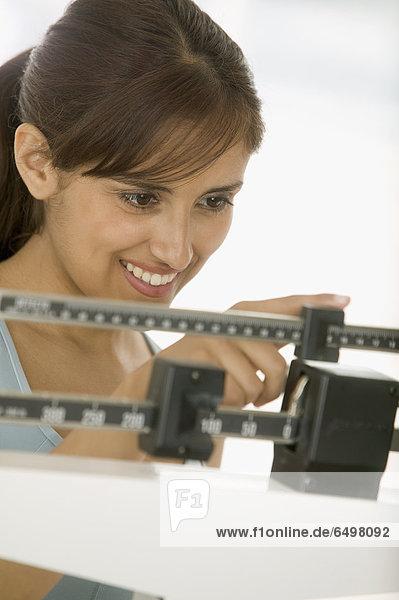 Frau mit einem Gewicht von selbst auf-Skala