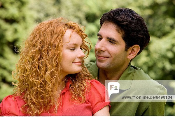 1247260 outdoor day summer park people woman young girl 20-25 blonde long haired smile smiling blouse red couple man 25-30 dark haired blouses green rest relax horizontal close up portrait