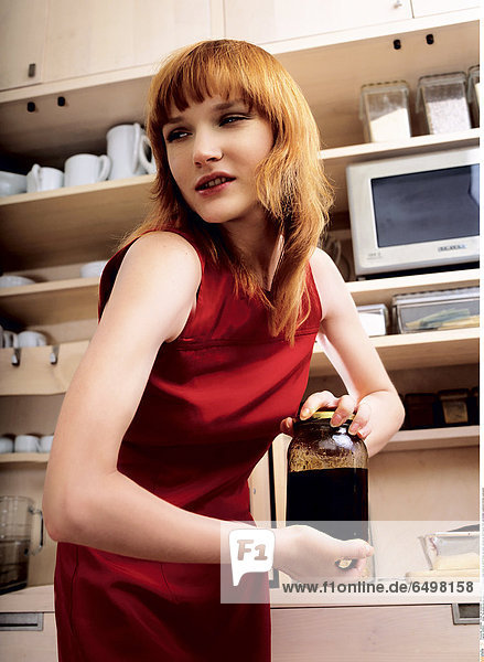 1246502 indoor flat people woman young girl 20-25 blonde fringe close up stand dress red open vertical jar hand hands hold jam kitchen cupboard kitchen cupboards