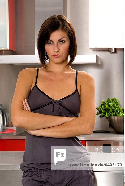 1247193 indoor flat kitchen people woman young 25-30 brunette close up blouse grey shorts smile smiling vertical