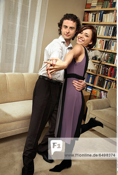 1248632 indoor flat room people woman brunette young 25-30 rest relax man couple dark haired dance blouse white tie black dress violet smile smiling hand hands hold shoe shoes vertical