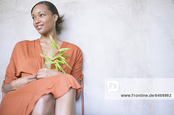 Woman sitting and holding plant