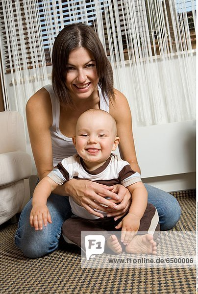 1252287 people two child girl boy woman mother motherhood son douther 0-5 25-30 years adult brunette bare foot feet tongue emotions happyness joy pleasure mime smile smiling indoor living-room vertical
