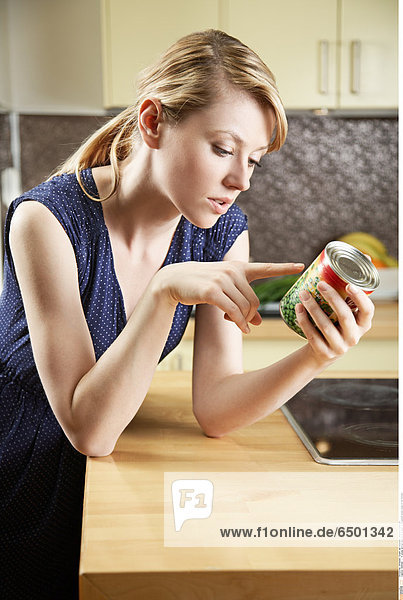 1256365 A young woman looking at a label on a canned green peas in the kitchen.