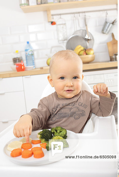 1266337 Little boy eating vegetables