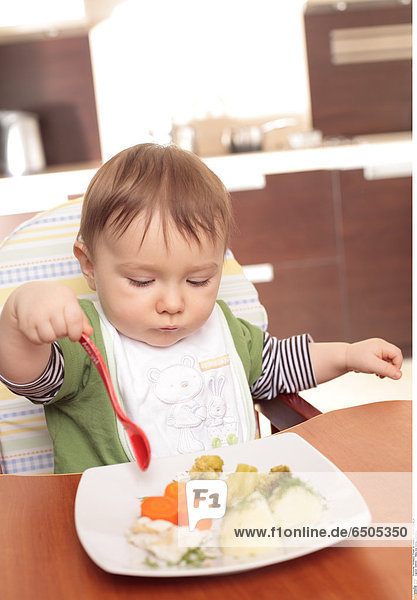 1266154 Baby boy eating vegetables
