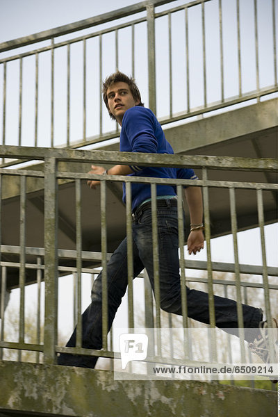 Mandatory Credit: Photo by John Powell / Rex Features ( 1041023d ) Model released - Young man running past railings Various